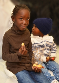 Genießt: Die zehnjährige Fatou probiert mit ihrem kleinen Bruder Moustafa die ersten Weihnachtskekse ihres Lebens.