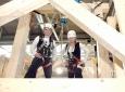 """Geeignete Absturzsicherung für Zimmerer muss ein selbstverständlicher Standard sein. Das Bild zeigt den Zimmerer-Welt- und Europameister Simon Rehm und die Künstlerin Kirsten Lossin auf der Internationalen Handwerksmesse IHM 2017. Quelle: """"Berufsgenossenschaft der Bauwirtschaft, Dieter Schnöpf"""""""