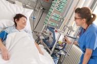 Patientin mit schwerer Herzschwäche auf der neuen Wachstation (Advanced Heart Failure Unit (AHFU). Eine Ärztin prüft die Versorgung mit einer minimal-invasiven Herzlungenmaschine (Cardiohelp-System). Bild: Universitätsklinikum Heidelberg.