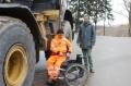 Der querschnittsgelähmte Rafael Spitz bereitet sich auf seinen Einsatz im 25-Tonnen-Radlader vor. An seiner Seite der Reha-Manager Stefan Kalkbrenner, BG BAU.   Foto: BG BAU, Fotograf: Bruno Streitmatter.