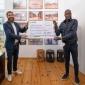 Mathias Hevert, Geschäftsführer von Hevert-Arzneimittel GmbH & Co. KG und Vorstand der Hevert-Foundation (links) überreicht Francis Kéré, Geschäftsführer Kéré Architectures einen Spendenscheck über 100.000 Euro.